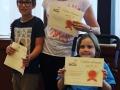 2 jeunes adhérents de la section natation et leur entraineur posent avec leur diplômes
